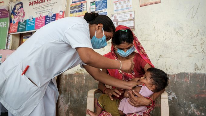 a small child, being held by her mother, is given a vaccine by a nurse in India