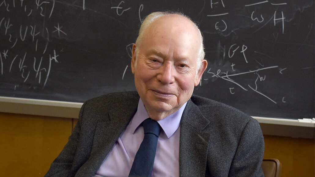 Steven Weinberg sitting in front of a chalkboard covered in equations