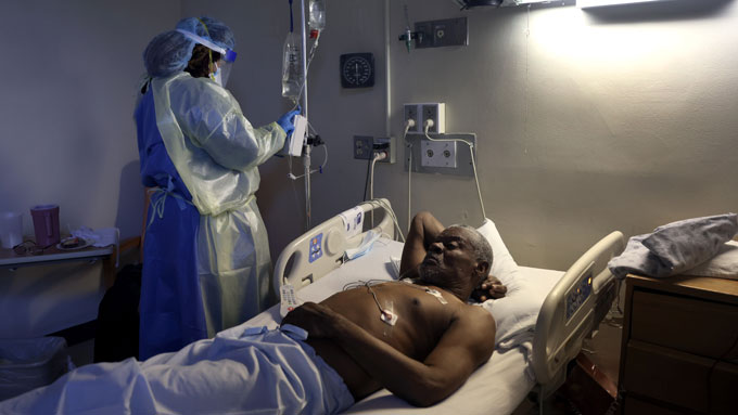 Curtis Jones lies in a hospital bed and receives a dose os remdesivir