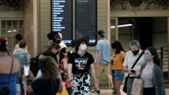 a crowd of people wearing face masks in Grand Central Station in New York City