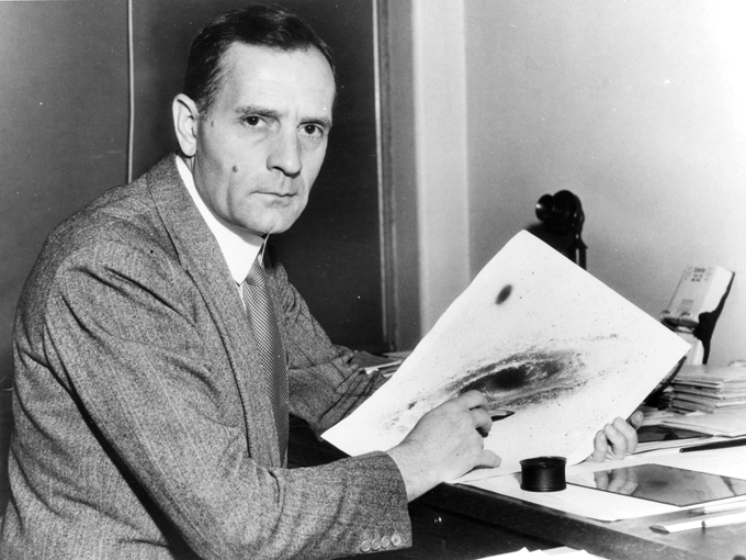 black and white image of Edwin Hubble sitting at a desk