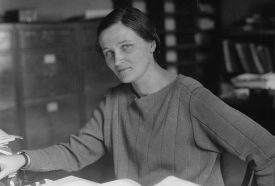 black and white photo of Cecilia Payne seated at a desk looking at the camera
