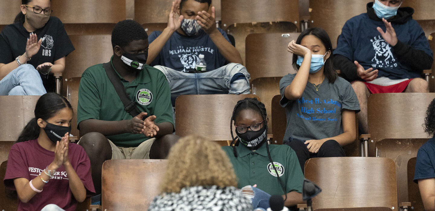 A small group of students in a lecture hall, wearing masks, with empty chairs between them. Several are applauding