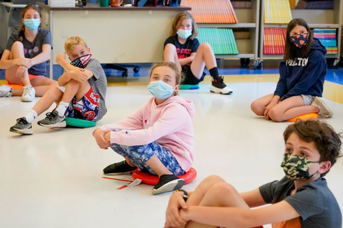 group of young children sitting on the floor, spread out and wearing masks