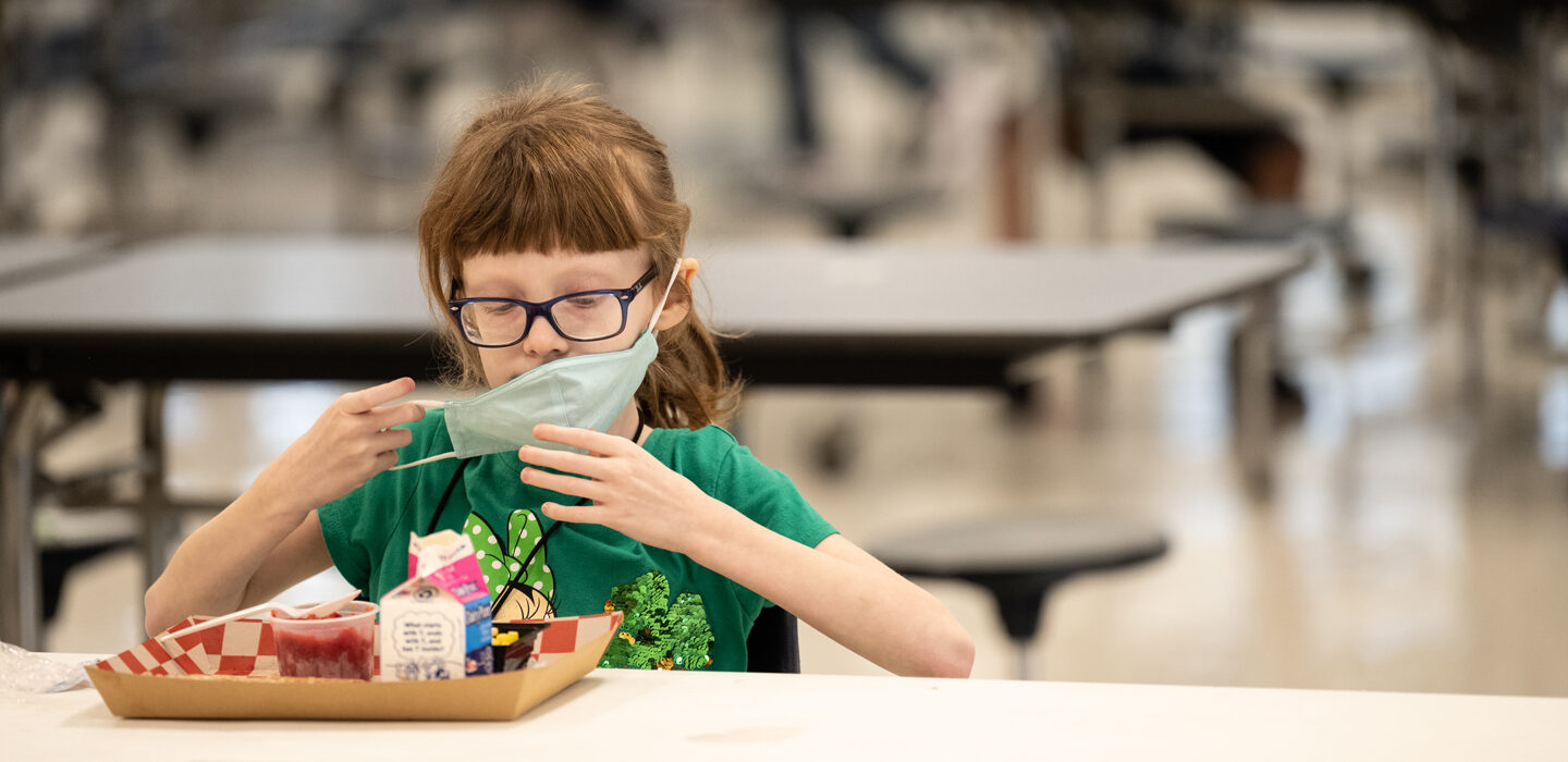 child removing a mask to eat lunch in a school cafeteria