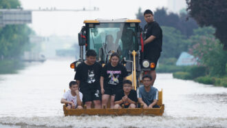 people riding in a backhoe amid flooding in China