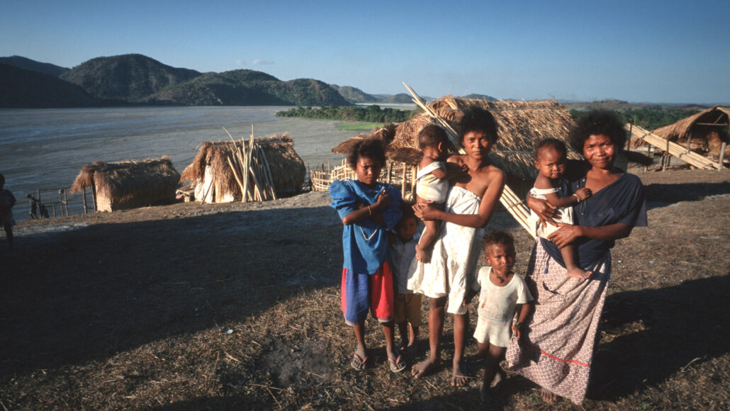 a group of Ayta people in front of huts beside a river