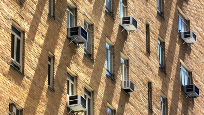 grid of window air conditioning units outside a Manhattan building