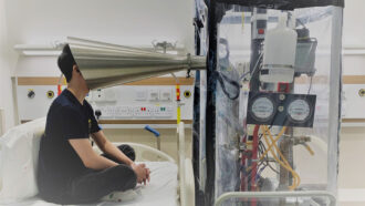 a researcher sits crosslegged on a hospital bed with their face inside a silver cone that's connected to a transparent chamber full of scientific apparatus