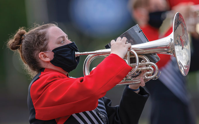 a marching band member wears a mask while playing the flugelhorn