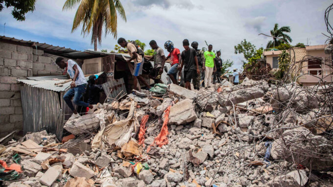 people climb over building rubble in Les Cayes