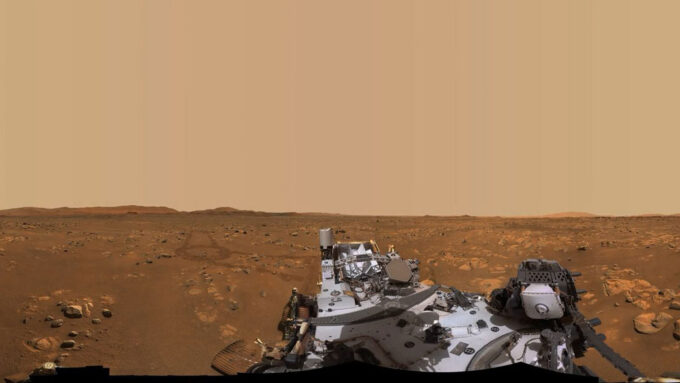 A photo of the Martian landscape with part of the Perseverance rover in the foreground