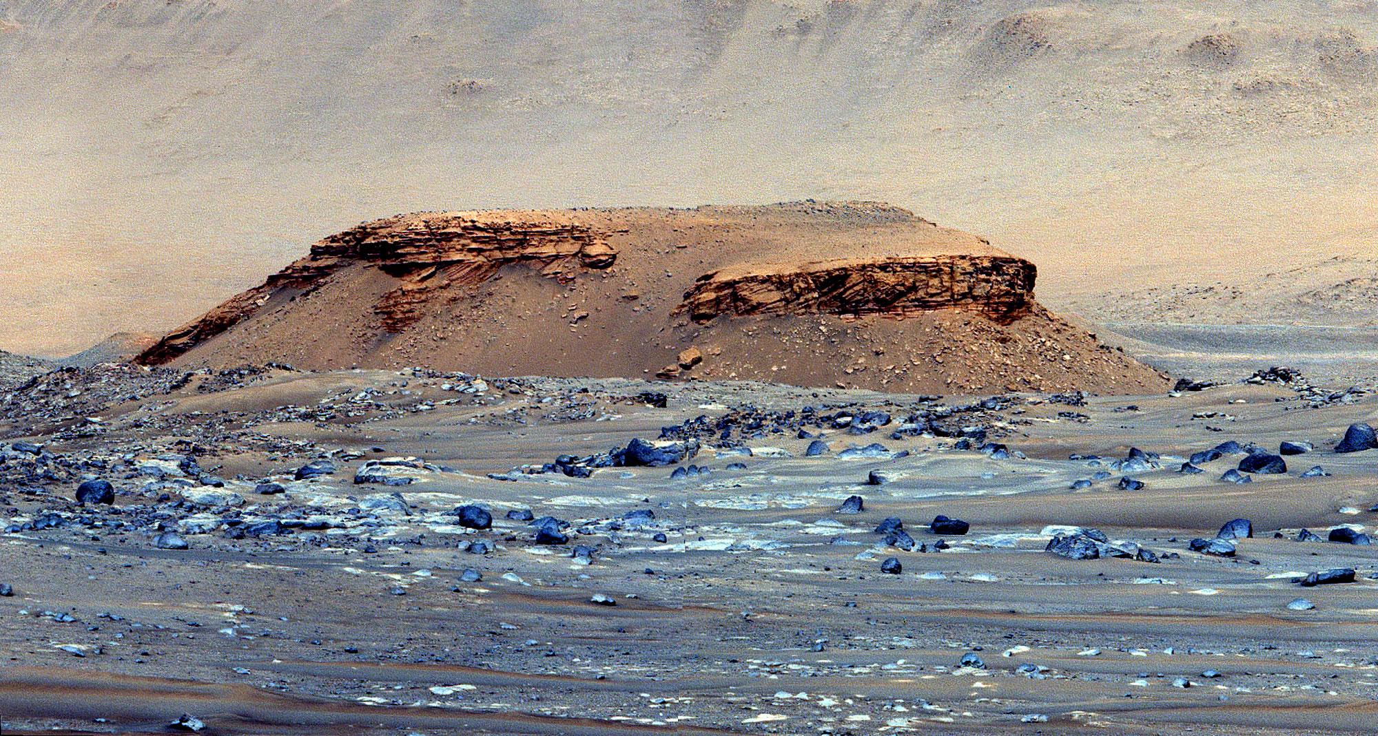 Lanskap kasar dengan bukit datar besar muncul dari tengah