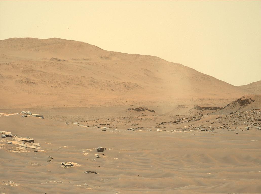 Setan debu seperti badai berputar melintasi lanskap cokelat di Mars