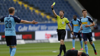 a referee holds up a yellow card amid during a soccer game in Germany