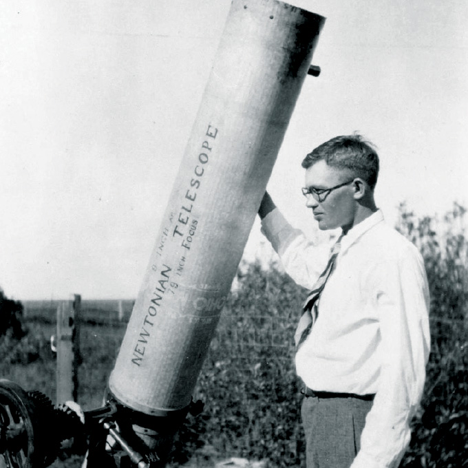 Clyde Tombaugh standing outside next to his telescope