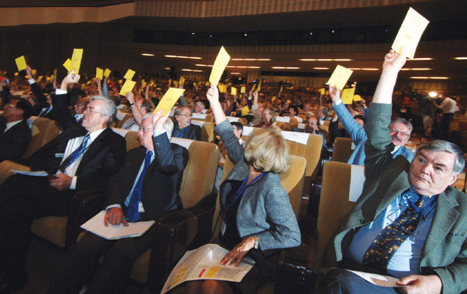 members of the International Astronomical Union hold up yellow cards to vote in an auditorium