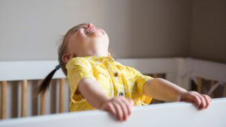 Baby wearing yellow, laughing with head tilted upwards