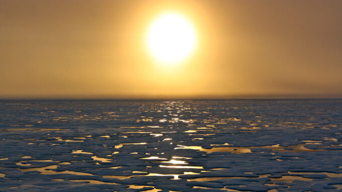 looking out over icy, flat terrain with sun in sky