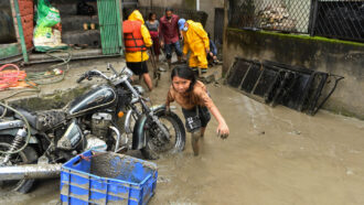 person wading through flooded Bishnumati River, leaning on motorcycle