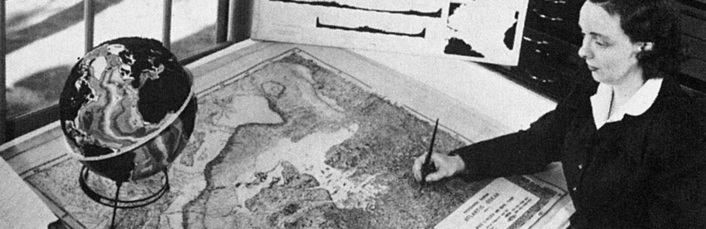 Marie Tharp at a desk drawing a map