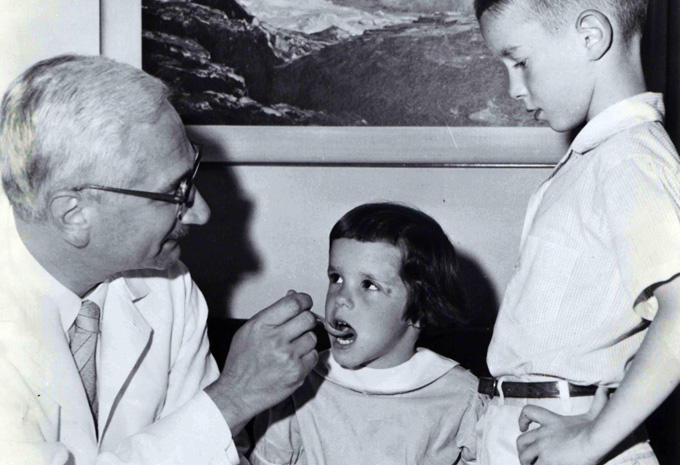 Albert Sabin giving a young child the polio vaccine, while another child waits