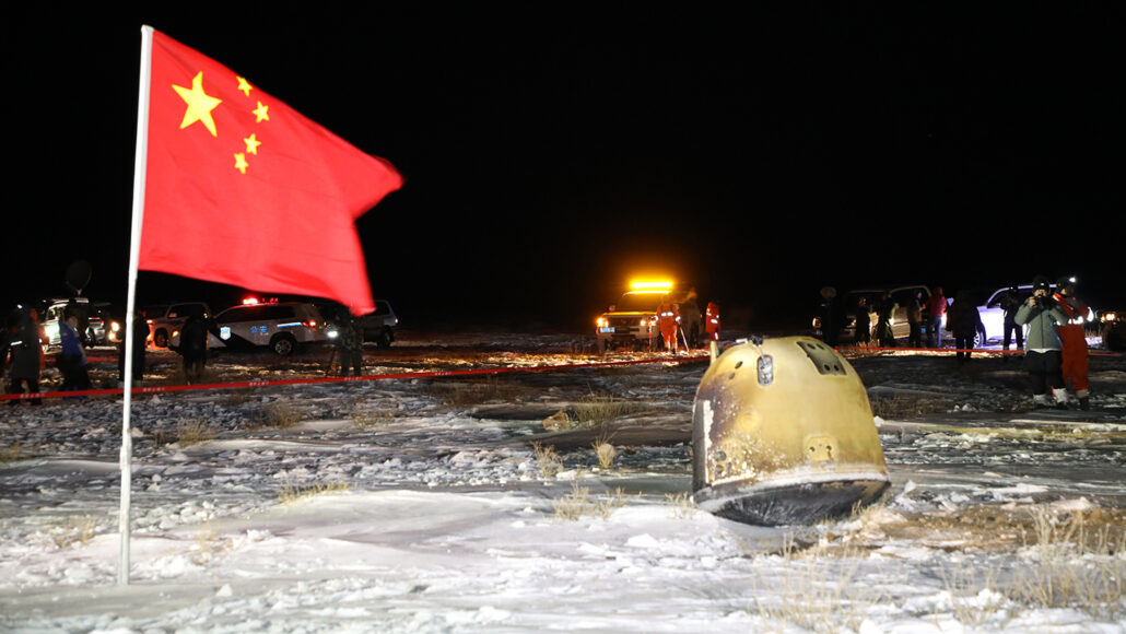 A capsule containing moon rocks next to a Chinese flag with vehicles in the background