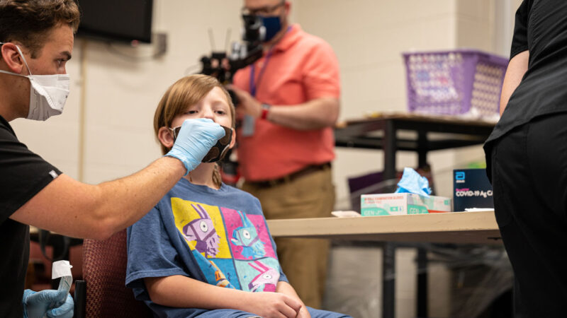 Elementary school student receiving a COVID-19 test from a person wearing a mask and gloves