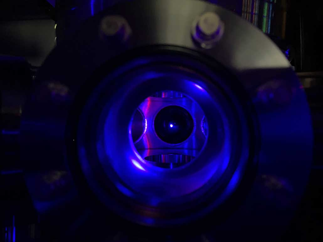 image of strontium atoms glowing blue in a vacuum chamber