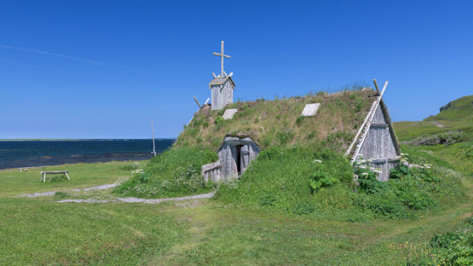 A reconstructed Viking Age hut with an overgrown roof in Newfoundland