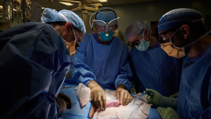 several doctors in scrubs and masks look at a patient on an operating table